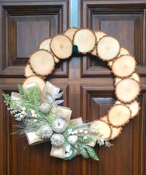 a wood slice Christmas wreath with silver frozen apples, faux greenery and berries