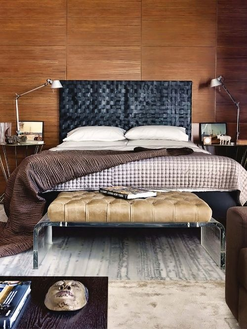 warm wood walls contrast a black leather woven headboard that brings texture in