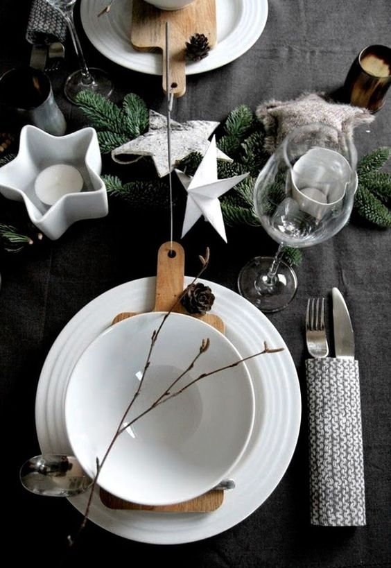 Scandinavian styled table with stars, candles, a knit utensil cover, pinecones and evergreens