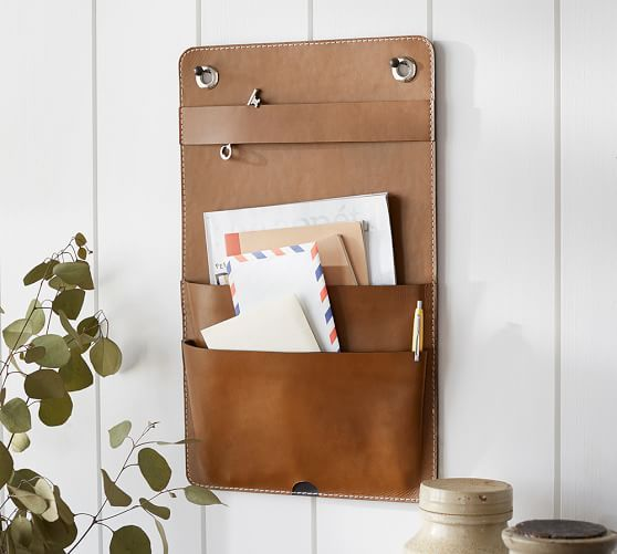 a brown leather wall storage piece for an entryway - put your keys and mail here