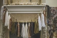 25 a metallic tassel garland over the fireplace and tinsel garlands