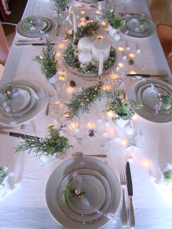 a neutral holiday table setting with lots of fresh greenery, ornaments, lights and candles