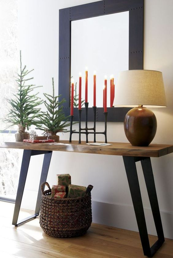 simple styling with evergreen trees, red candles and a basket with gifts