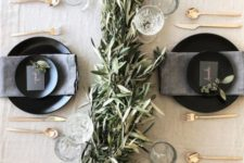26 a neutral tablescape with a greenery garland, glasses, matte black plates and chargers and gold cutlery
