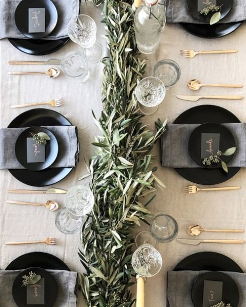 a neutral tablescape with a greenery garland, glasses, matte black plates and chargers and gold cutlery