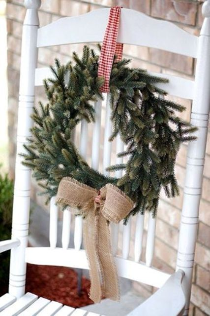 an evergreen wreath with checked ribbon and a burlap bow