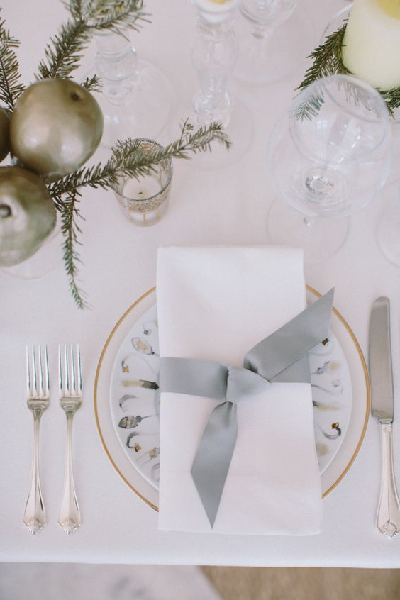 a neutral tablescape with metallic ornaments, evergreens, candles and printed plates