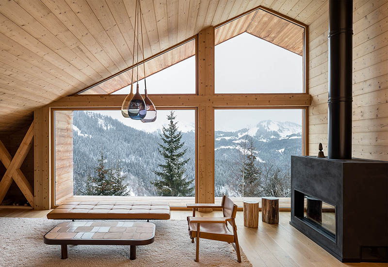 This is the living room of the chalet with a large sloped window, a large hearth and a selection of modern furniture