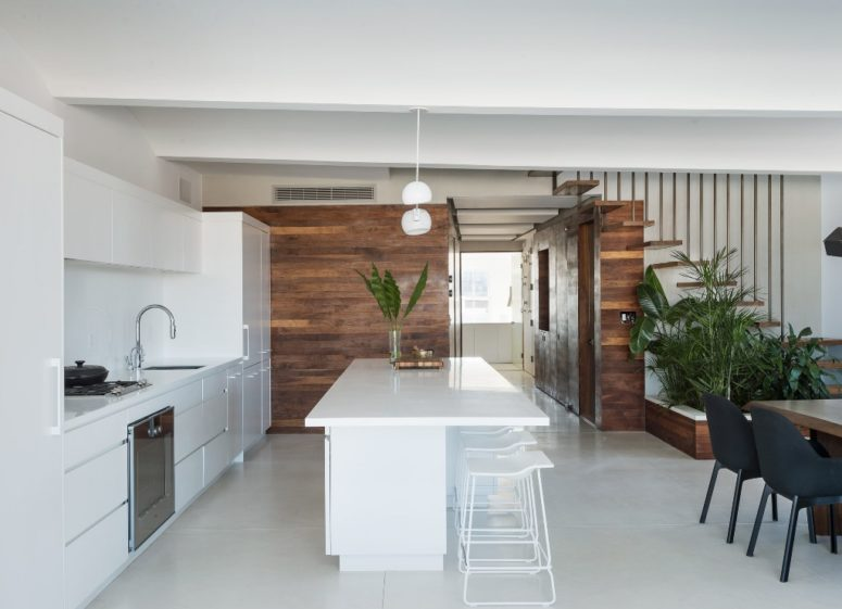 The kitchen is done with white cabinets and a white kitchen island, the wood clad walls create a contrast