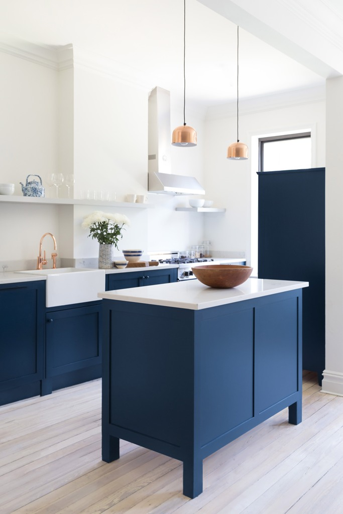 The kitchen was decorated with bold blue cabinets with marble countertops and glam was added with brass and copper touches