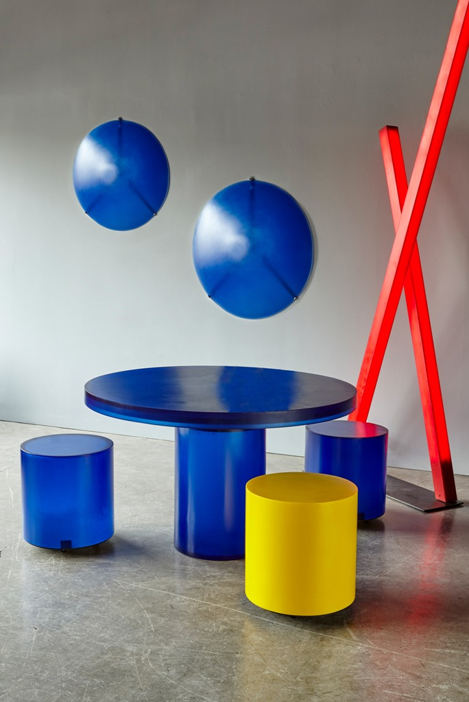 The round Chief stool has a cylindrical form, in blue, yellow or red, and the table has a circular surface and a single leg and is made from blue resin