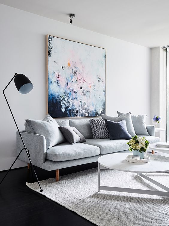 a bold oversized artwork over the sofa is a cool colorful statement