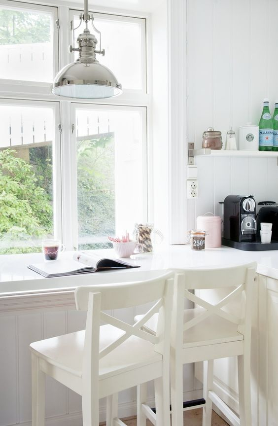 a kitchen counter is continued into a windowsill and is used as a breakfast bar