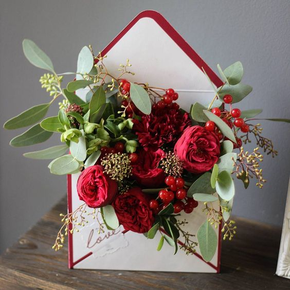 a stylish centerpiece of a burgundy lined envelope filled with bold blooms and greenery