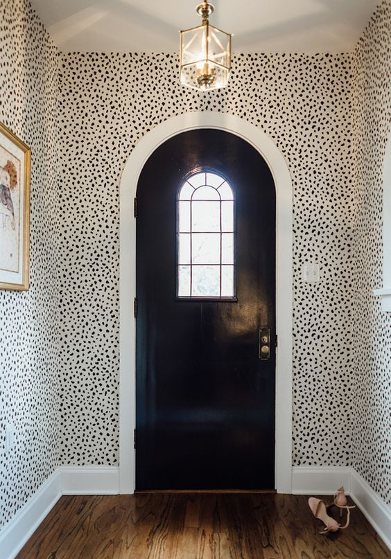 sophisticated mid-century modern entryway with Dolmatin print wallpaper and gilded touches