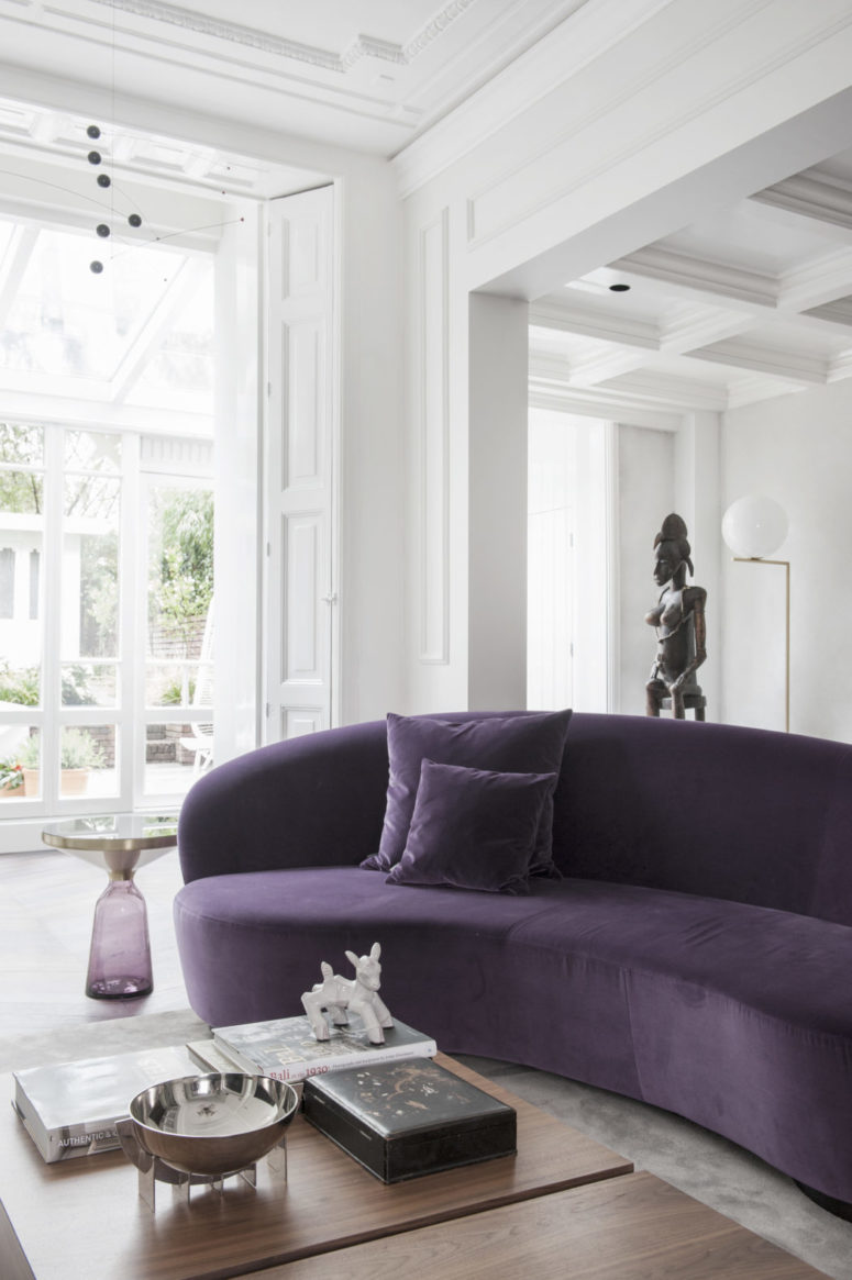Floor to ceiling windows make the space feel airy, and the deep purple sofa makes a colorful accent