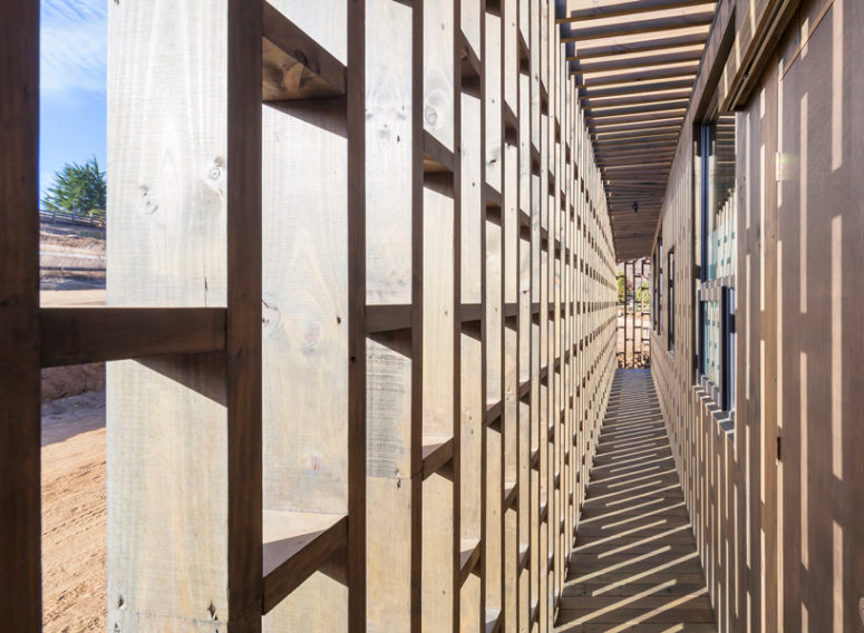 The building diminishes the wind with a second skin of wooden slats, which also provide some privacy as the house is fully glazed