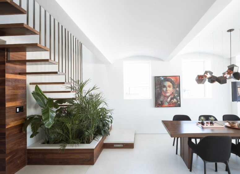 The dining zone is done with a mid-century modern dining set, eye-catchy geometric lamps and there's much greenery potted under the stairs