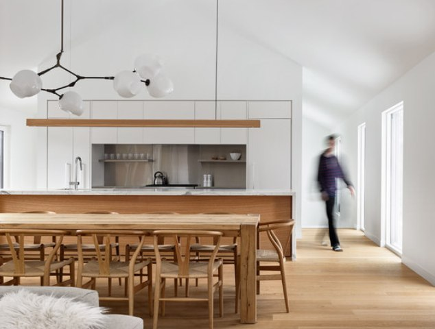 The kitchen features a white cabinets, a marble kitchen island and natural wood, of which the dining set is made too