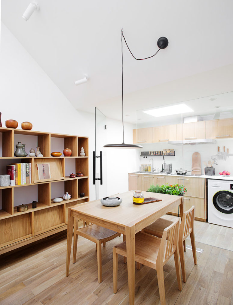 The kitchen is attic, with much light-colored plywood in decor, and there's a cozy dining space next to it