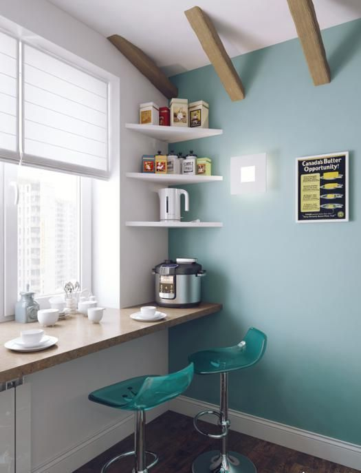 a modern breakfast space with bold turquoise chairs and a cork windowsill