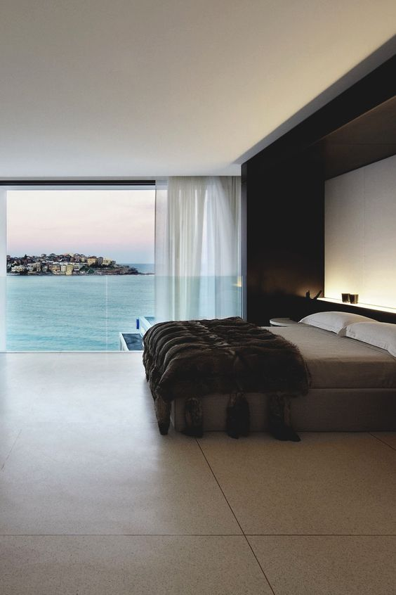 a spacious masculine bedroom with a gorgeous sea view