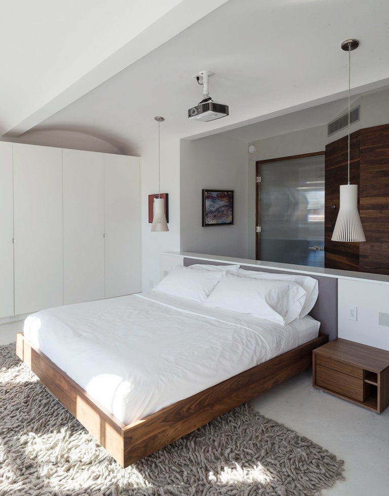 One of the bedrooms with a floating bed, pendant lamps and a wardrobe with natural wood touches