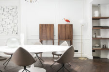 The dining space features a geo artwork, some wooden cabinets, built-in shelves and a modern dining zone with egg-like chairs