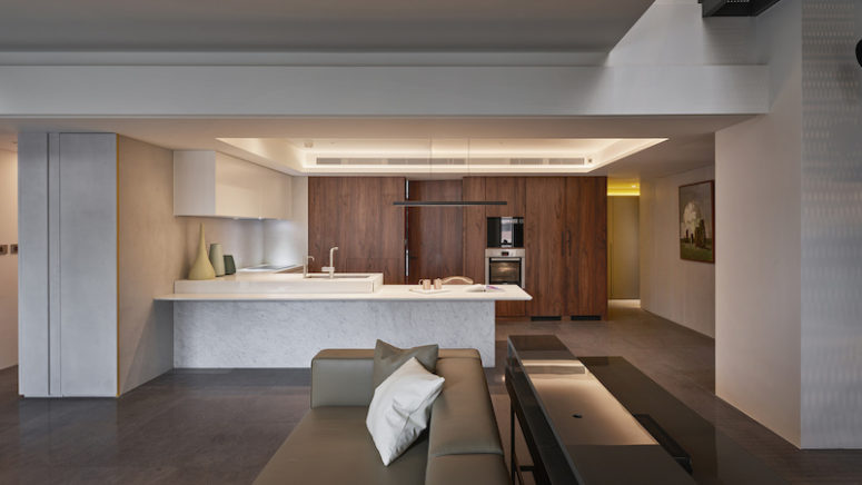 The kitchen features rich-colored wooden cabinets and white ones plus a marble kitchen island