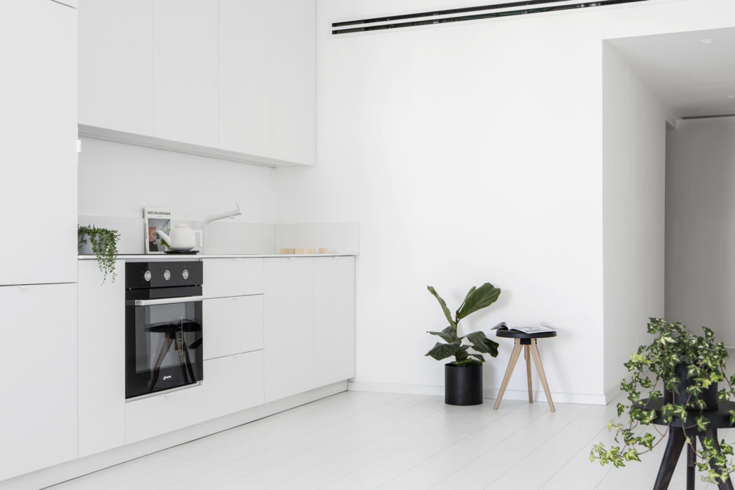 The kitchen is done with sleek white cabinets and lots of potted greenery enliven the minimalist space