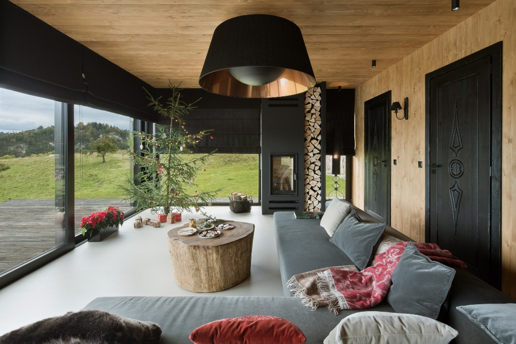 The living room features a hearth with firewood, a large grey corner sofa and a large tree stump table