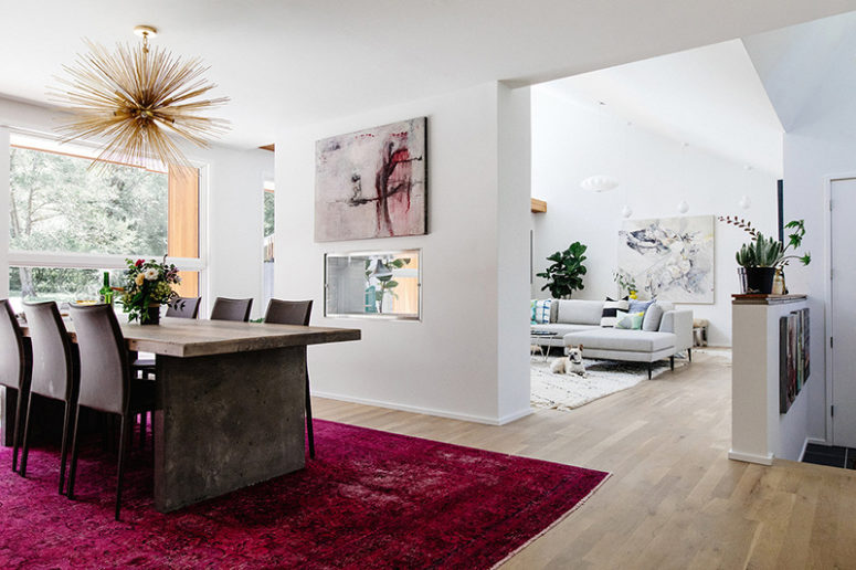 The living room is partly divided from the dining room with a fuchsia rug, a bunburst chandelier and a bold artwork