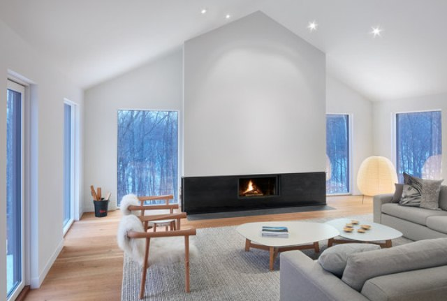 The living zone is done with many windows to enjoy the views, a separate fireplace wall as a centerpiece