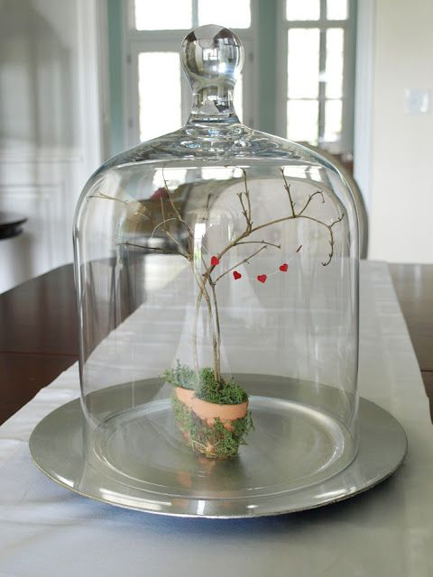 a cute centerpiece of two planters with moss, branches and a little red heart banner