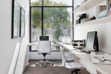 a modern shared home office with a floating desk for two and shelves over it