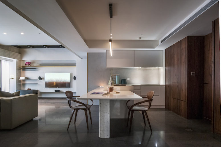 A dining table is attached to the kitchen island and is perfectly integrated into the kitchen zone