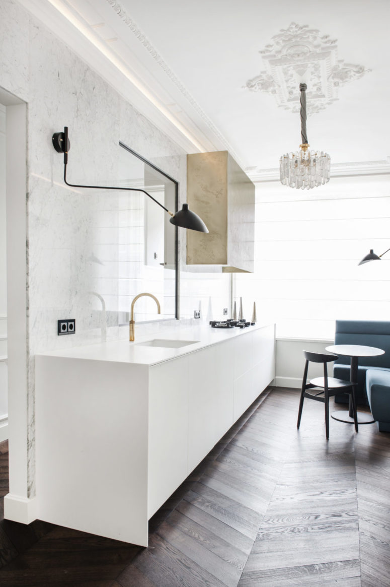 The kitchen is done with a marble backsplash, a white cabinet, a hanging metallic one and a bold glam chandelier