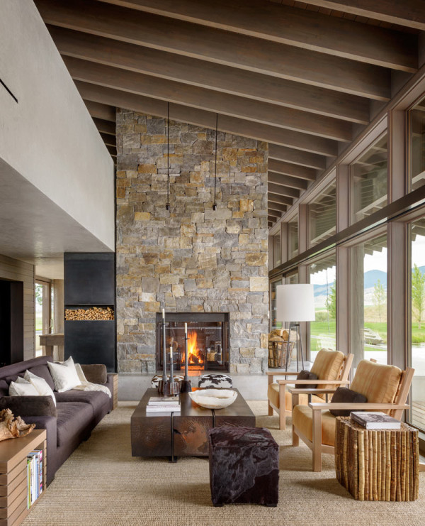 The living room features a large stone clad fireplace, some wooden furniture, faux fur and velvet that are used for a cozy feel