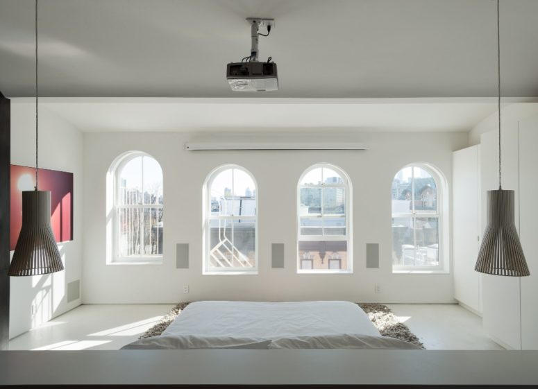 The master bedroom shows lots of windows that bring much light in and a bed placed on the floor