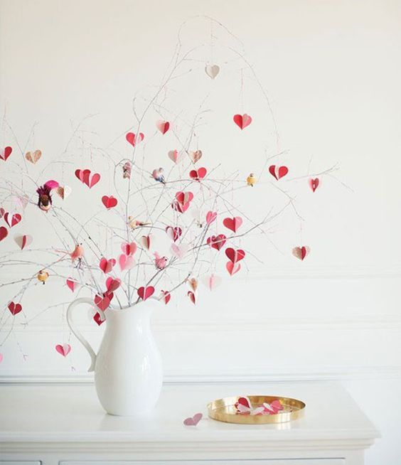 a modern Valentine's Day centerpiece of a white jug and pink, blush and gold hearts on branches