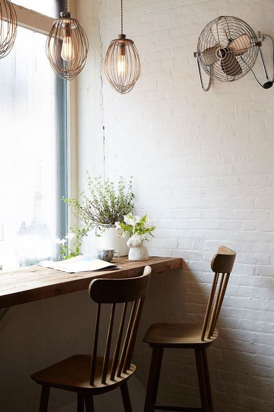 a wooden windowsill and chairs make an industrial space cozier