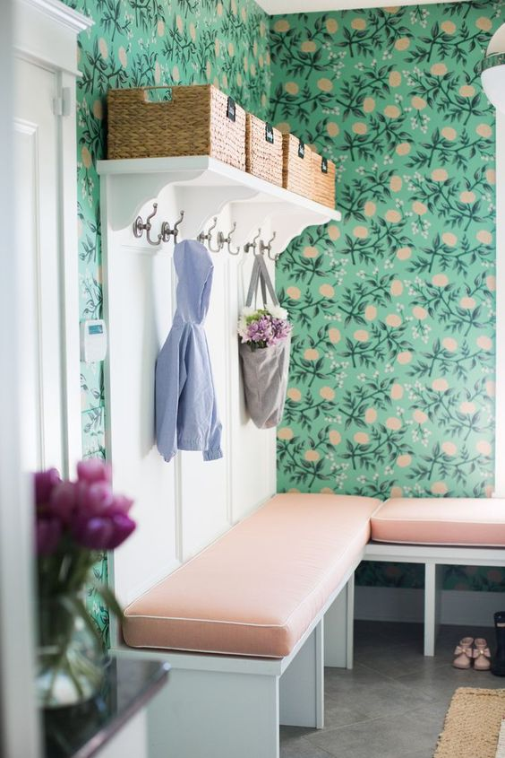 bold green wallpaper with a floral print and matching cushions on the benches