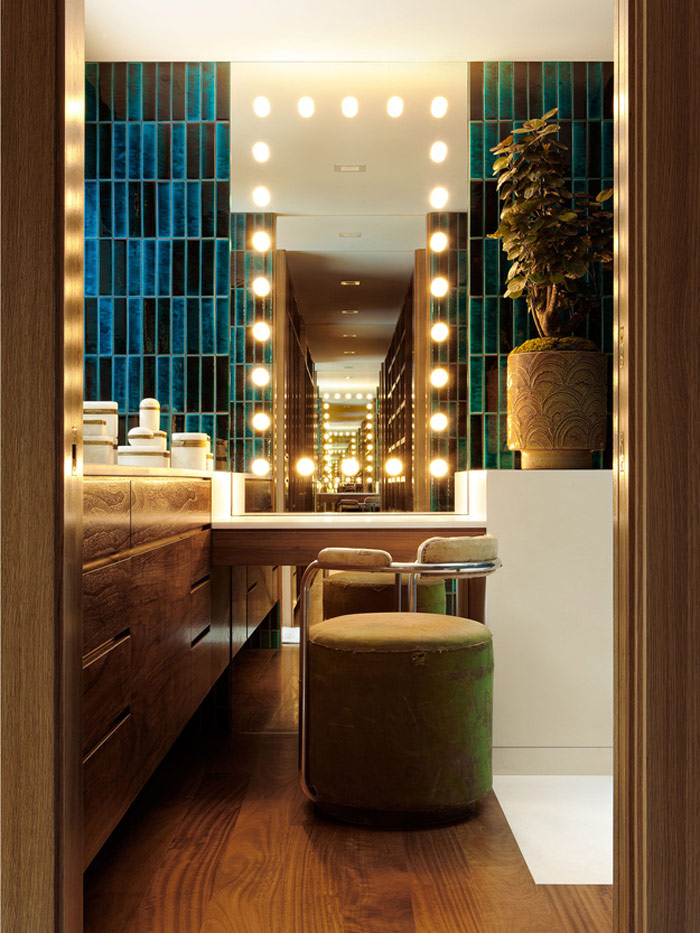 One of the bathrooms includes a makeup nook with a lit-up mirror and a comfy upholstered chair