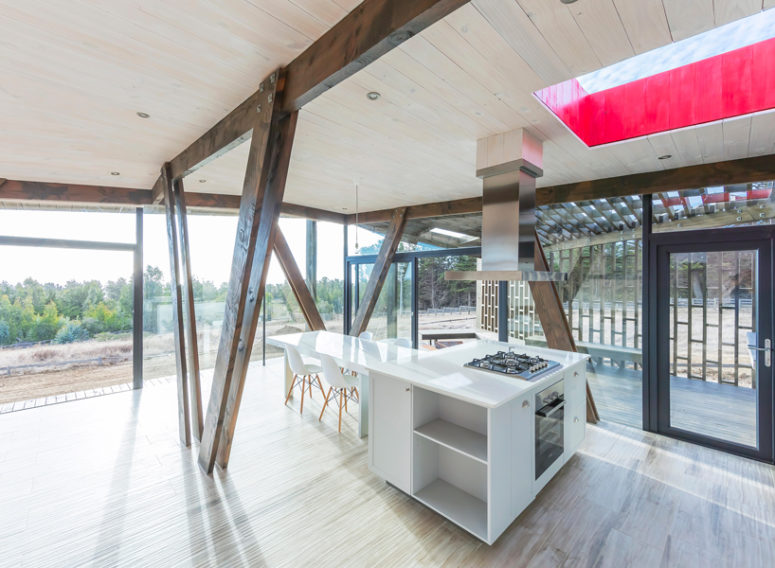 The kitchen is done with minimalist white furniture and wooden beams that echo with the wooden shell outside