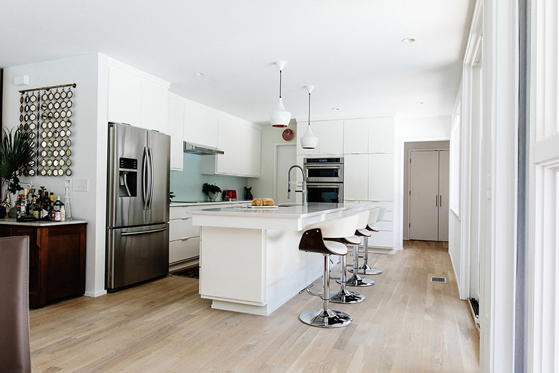 The kitchen with white cabinets and a large kitchen island is only visually separated from the dining room