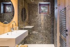 06 The master bathroom is clad with wood and stone-looking grey tiles, there's a shower space