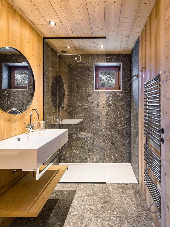 The master bathroom is clad with wood and stone-looking grey tiles, there's a shower space