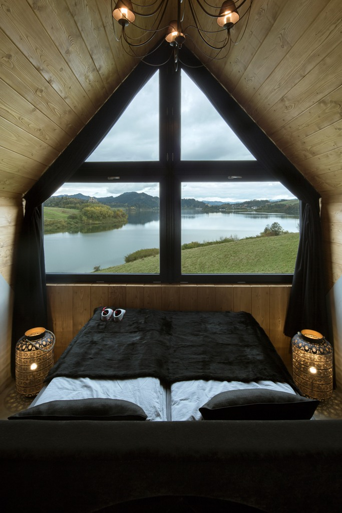 The master bedroom is centered around the views, there's an upholstered bed with some drawers and lanterns