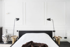 06 The master bedroom is done with white wainscot walls, black furniture and brass nightstands