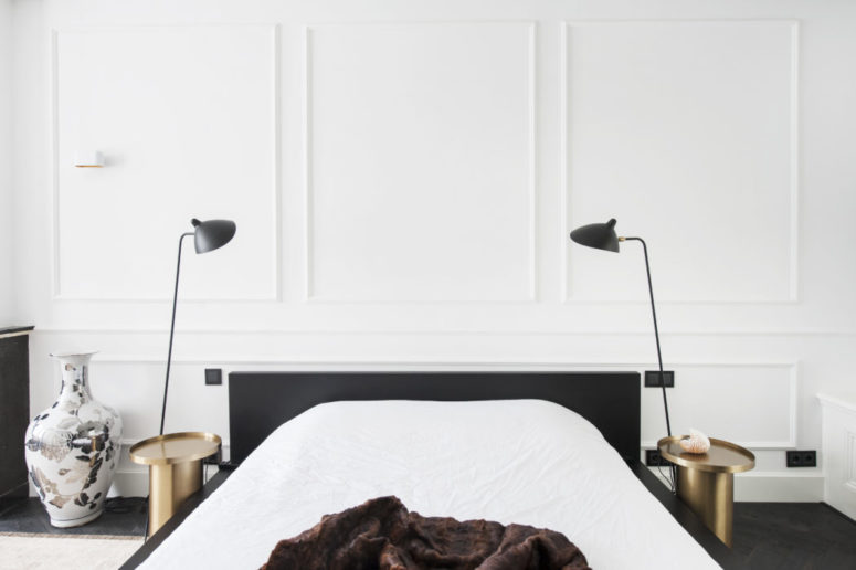 The master bedroom is done with white wainscot walls, black furniture and brass nightstands